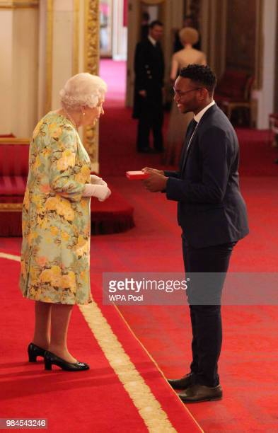 Mr Thamsanqa Hoza from South Africa receives his Young Leaders Award from Queen Elizabeth II during the Queen's Young Leaders Awards Ceremony at...