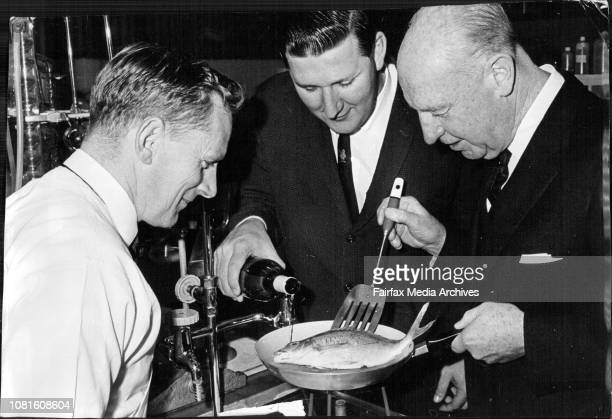 Mr Tyson at left in the modern laboratory of McWilliams as Sir Eric prepared the fish Sir Eric is at right and in the centre is Mr Don McWilliam...