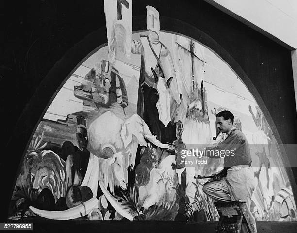 Mr W D J McDowell painting the finish touches on a mural representing the Spirit of the Empire at the North London Exhibition Alexandra Palace London...