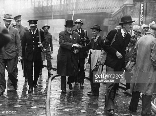 Mr Winston Churchill today visited the City where he inspedted damaged areas caused by last night's raid over London