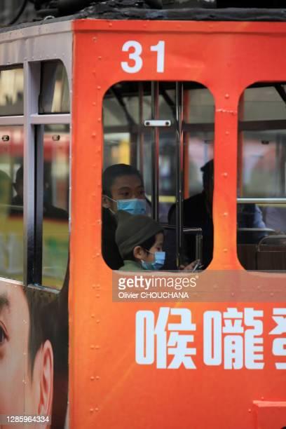 Mère et son enfant portant un masque de protection contre le Coronavirus dans un tramway le 29 janvier 2020, Hong Kong, Chine.