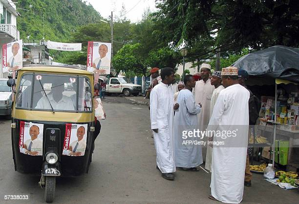 A rickshaw mototaxi speeds along a street in Mutsamudu 13 April 2006 the capital of Anjouan Island in the Comoros archipelago while supporters of...