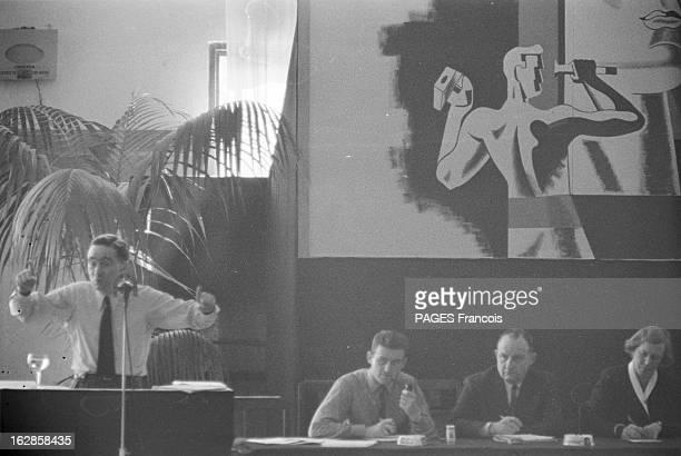 Mrp Congress En 1954 un homme non identifié derrière un pupitre et des micros s'adresse avec des gestes aux membres du Mouvement Républicain...