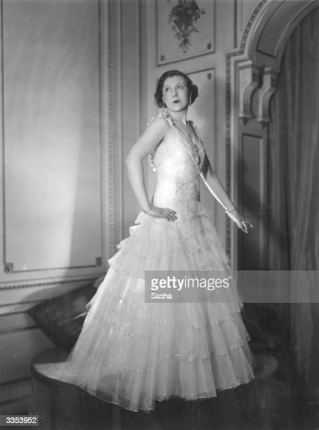 Mrs A G McCorquodale, aka English romantic novelist Barbara Cartland , wearing an evening dress.