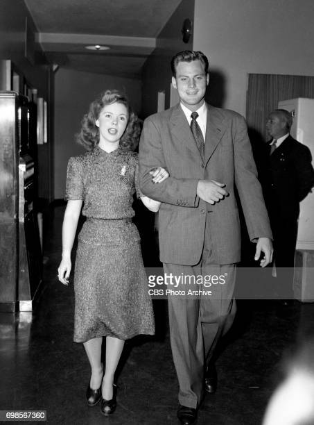 Mrs and Mr John Agar saunter through the corridor of Columbia Square to the broadcast studio In background at right is George Temple Shirleys father...
