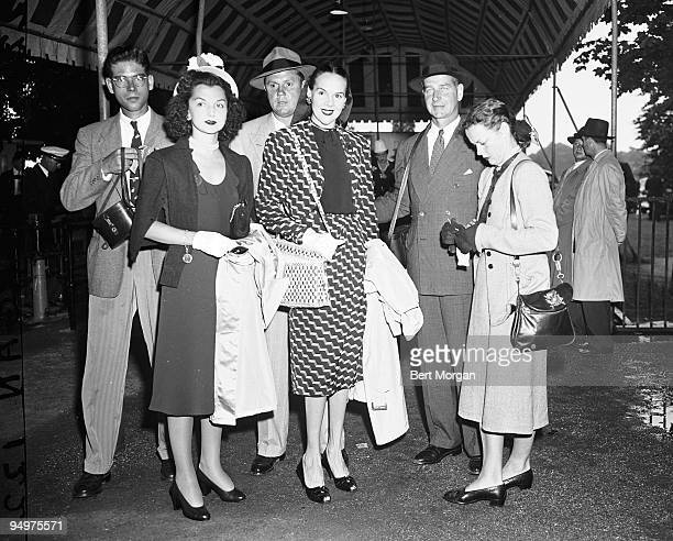 Mrs and Mrs John Sims Kelly Mrs and Mr CV Whitney and Mrs Bertrand L Taylor standing under a tent the Empire Club Belmont Park Flushing Meadow NY...