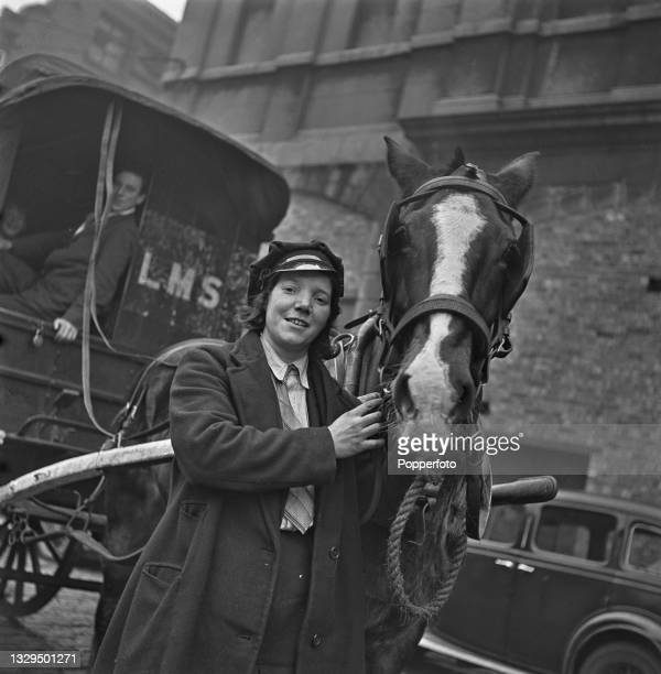 Mrs Ann Bennett, a London, Midland and Scottish Railway delivery driver, stands beside her horse and cart in Liverpool, England during World War II...