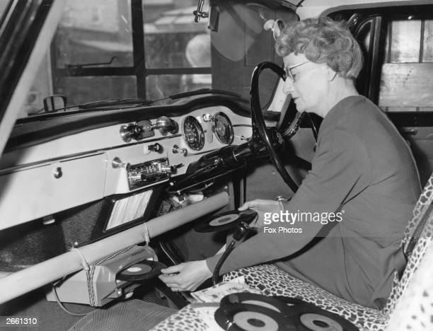Mrs Batt inserting a record into the front of her incar record player The music is fed into the car radio speaker system