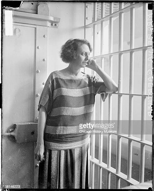 Mrs Belva Gaertner standing and looking through jail cell bars Chicago Illinois March 13 1924