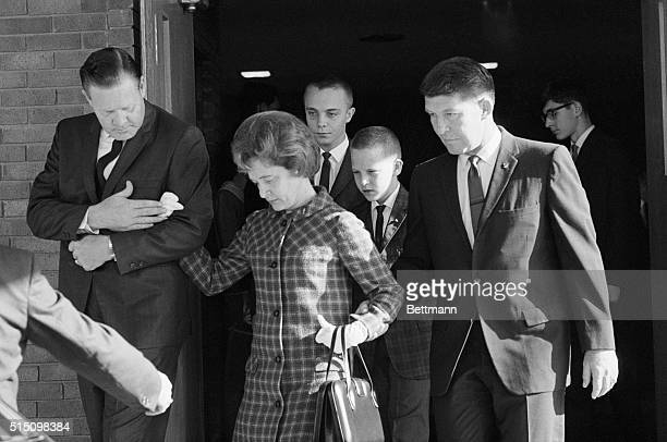 Mrs Betty Grissom escorted by astronaut Wally Schirra and accompanied by her two sons Scott and Mark leaves memorial services for her late husband...