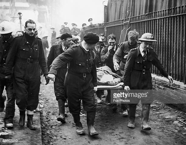 Mrs Bowley the wife of a school caretaker shakes the hand of her rescuer Johnny Driscoll of an ARP rescue team as she is carried away on a stretcher...