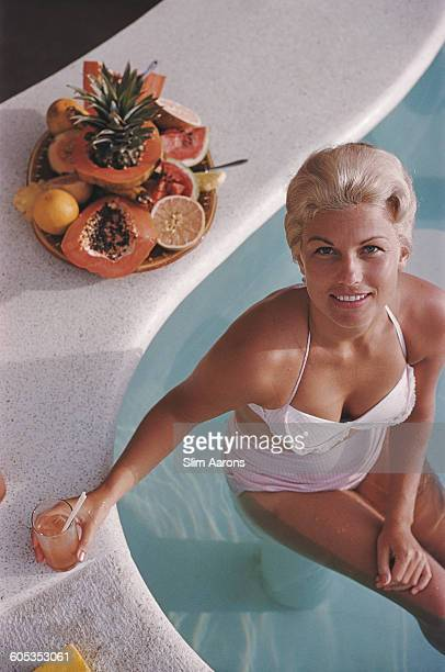 Mrs Charles Rogers sits on a submerged bar stool in the Villa Vera Spa Racquet Club pool Acapulco Mexico January 1961
