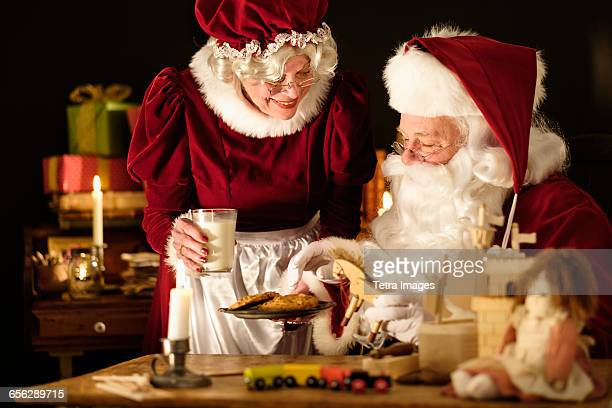 Mrs. Claus bringing homemade cookies to Santa Claus
