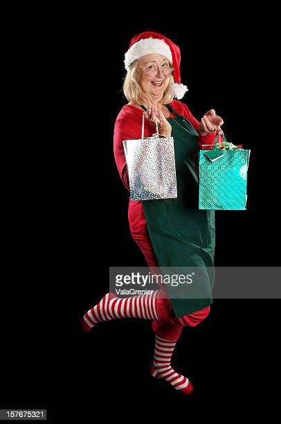 signora natale ballando con regalo. - mamma natale foto e immagini stock