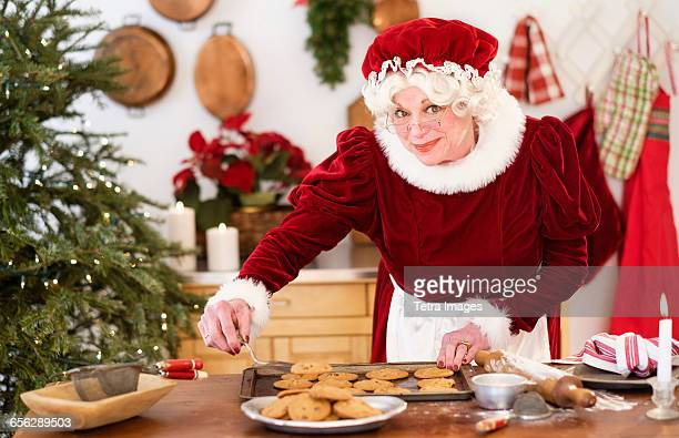 mrs. claus making gingerbread cookies - mere noel photos et images de collection