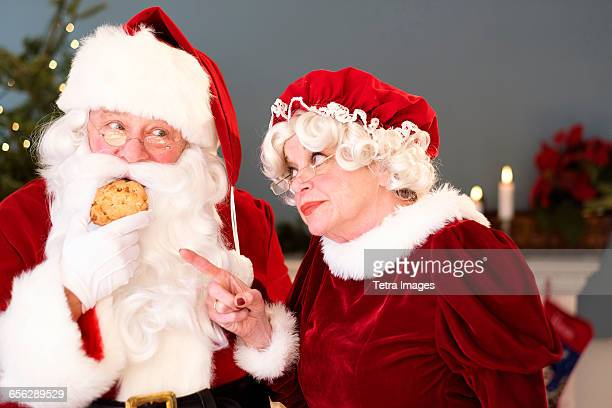 Mrs. Claus pointing on Santa eating gingerbread cookie