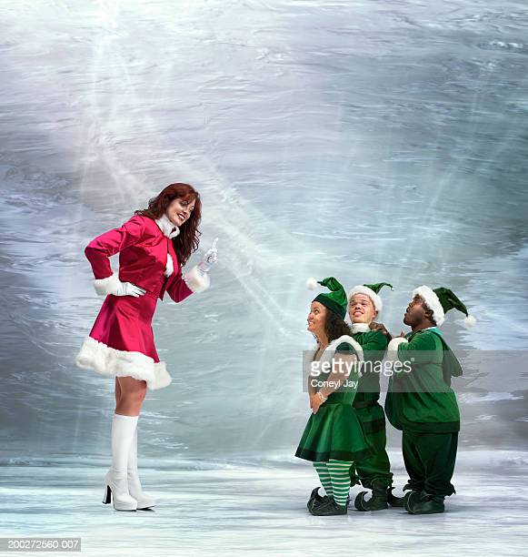 'mrs claus' waving finger at three 'elves' (digital composite) - naughty santa stock photos and pictures