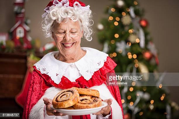 weihnachtsfrau mit zimtbrötchen - weihnachtsfrau stock-fotos und bilder