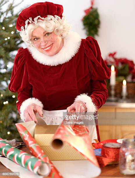 mrs. claus wrapping christmas gifts - mamma natale foto e immagini stock