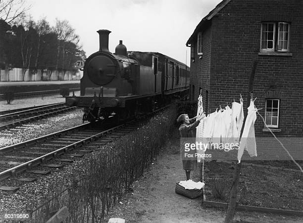 Mrs Cordery, the wife of a railway worker, hanging out her washing in her garden, which is situated between two main railway lines at Ascot station,...