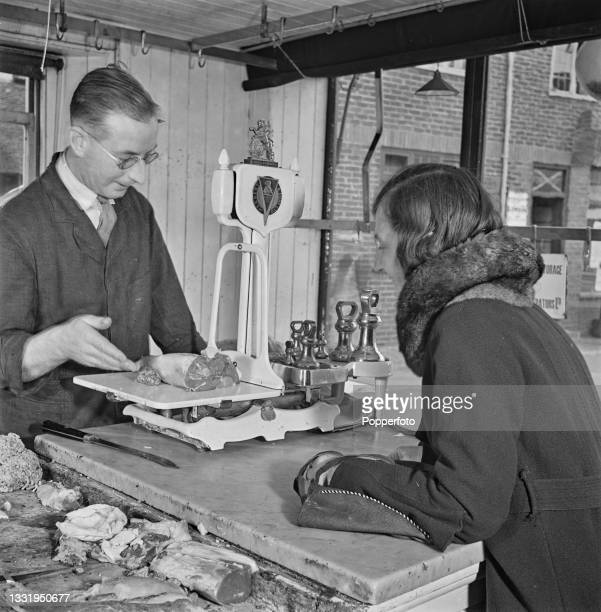 Mrs Daisy Towner, the wife of a farm labourer, buys her weekly ration allowance of meat for her family from her local butcher in East Malling, Kent,...