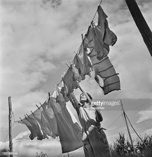 Mrs Daisy Towner, the wife of a farm labourer, hangs out her laundry and washing to dry on a line at home in East Malling, Kent, England during World...