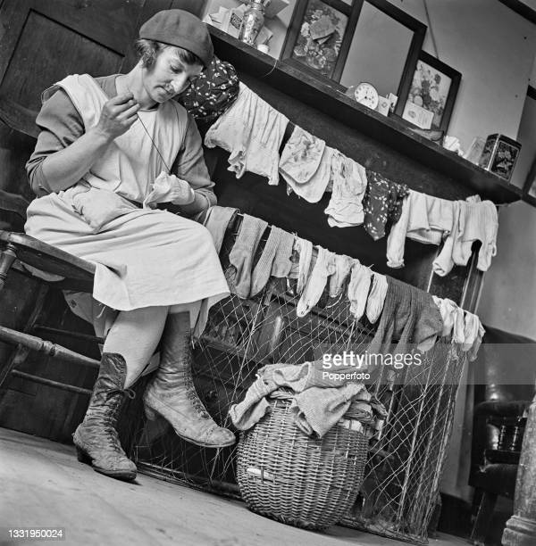 Mrs Daisy Towner, the wife of a farm labourer, mends her family's socks and stockings drying in front of the grate at home in East Malling, Kent,...