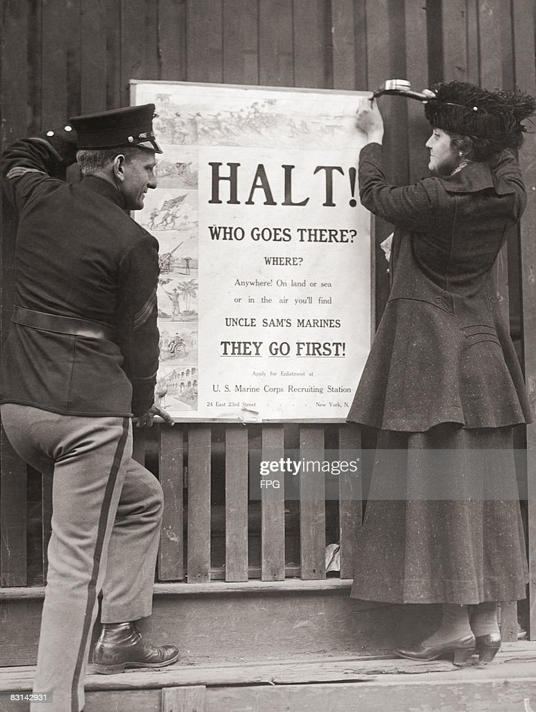Mrs Davis B. Wills, the wife of a US Marine Corps captain, nails up a recruitment poster for the corps, New York, circa 1918.