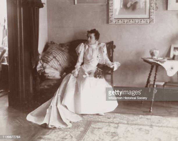 Mrs DW Osborn sits on a loveseat in a Victorianera home Madison Wisconsin 1896 She sits in her wedding dress with a bouquet of flowers on her lap