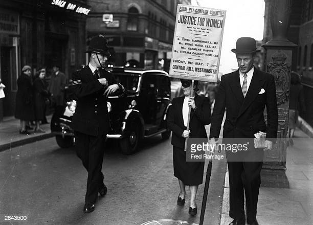 Mrs Edith Goulden Bach leading a group of masked women in a poster parade along the Strand to advertise a meeting calling for equal pay rights for...