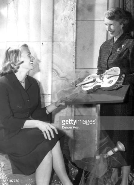 Mrs Edward Bennett Close Jr chairman of the Symphony Jewel ball ticket committee admires a jeweled violin displayed by Mrs James William Gaynor the...