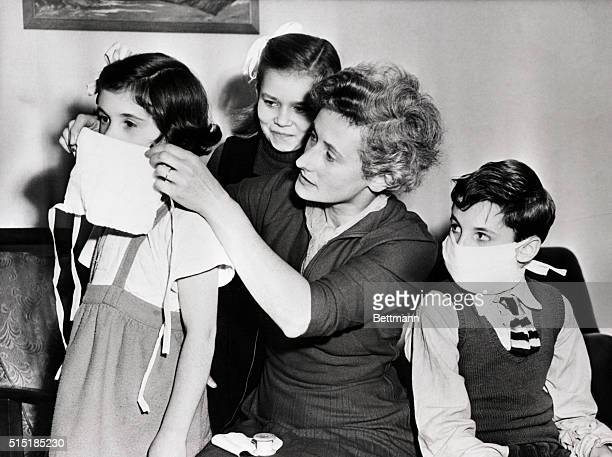 Mrs. Eileen Frayne equips her children with surgical gauze outfits, designed to specifications advocated by London physicians. Ministry of Health,...
