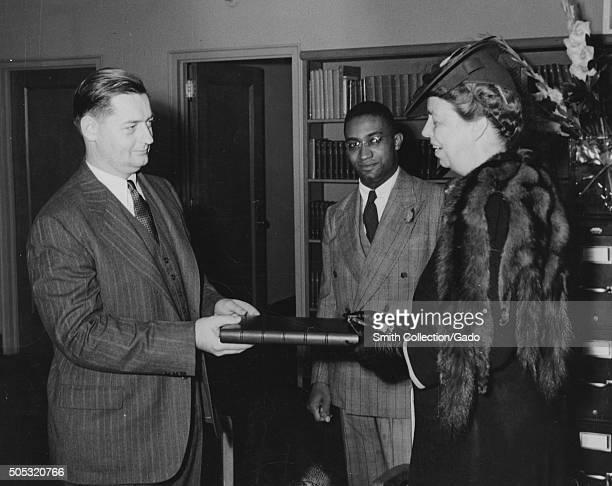 Mrs Eleanor Roosevelt presenting the President's manuscript copy of the radio address on the Atlantic Charter Mr Francis R St John Chief of...