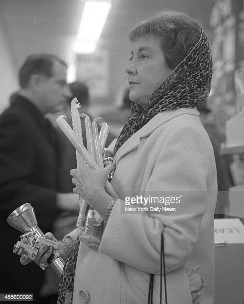 Mrs Evelyn Cavarape loaded down with candles batteries and a flashlight waits in line to pay for her purchase at Korvette's E 44th St She and many...