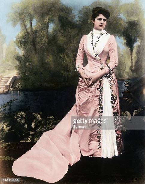 Mrs Frances Cleveland in a formal dress She is shown full length with trees and water in the background Undated handcolored photograph