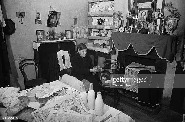 Mrs Francis sits in her cluttered living room on Christmas Street southeast London 21st December 1946 Widowed for many years she helps out her...