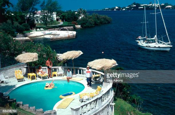 Mrs Frank McMahon and guests around the pool at her seaside home in Bermuda 1977