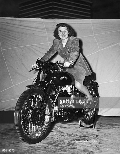 Mrs Frankie Roberts straddles a Vincent Black Lightning at the Cycle and Motorcycle Show at Earl's Court 21st October 1949 The 1000cc V twin reaches...