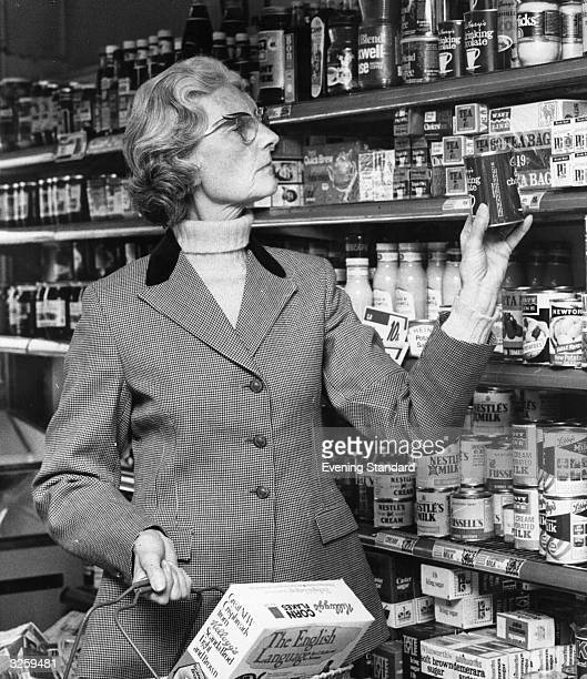 Mrs Godber in her riding gear examines a tin of Cadbury's drinking chocolate while shopping in a Wavy Line supermarket