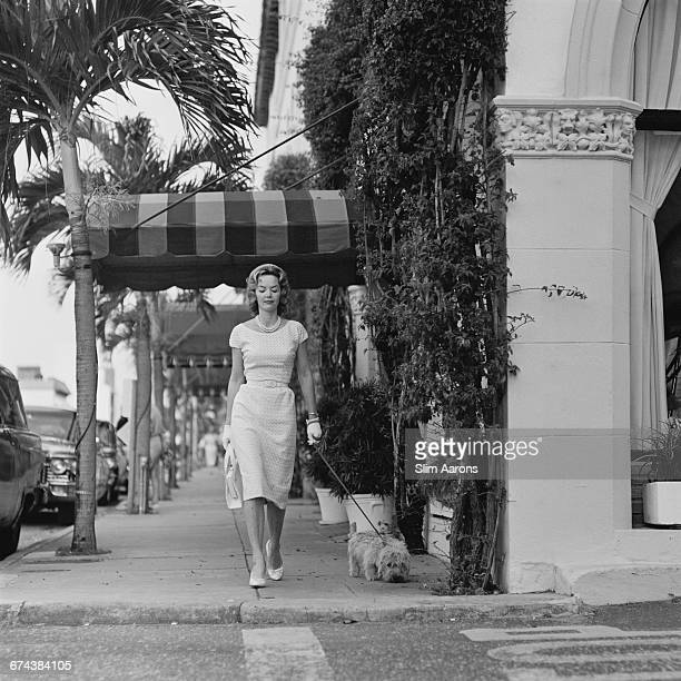 Mrs. Guilford Dudley, JR. Wears a De De Johnson lace dress as she walks her Dandie Dinmont Terrier 'Tiger' on Worth Avenue, Palm Beach, Florida,...
