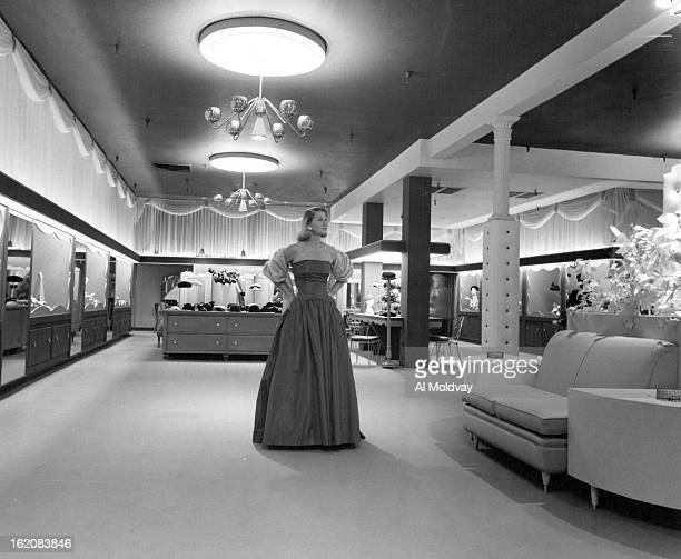 OCT 28 1956 Mrs H T Kimbell models high fashion in evening wear in GanoDowns new fourth floor women's department featuring luxurious decor and...