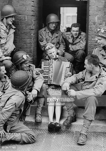 Mrs Hale the wife of a British soldier fighting in Europe plays the accordion outside her house for a group of American soldiers shortly before their...