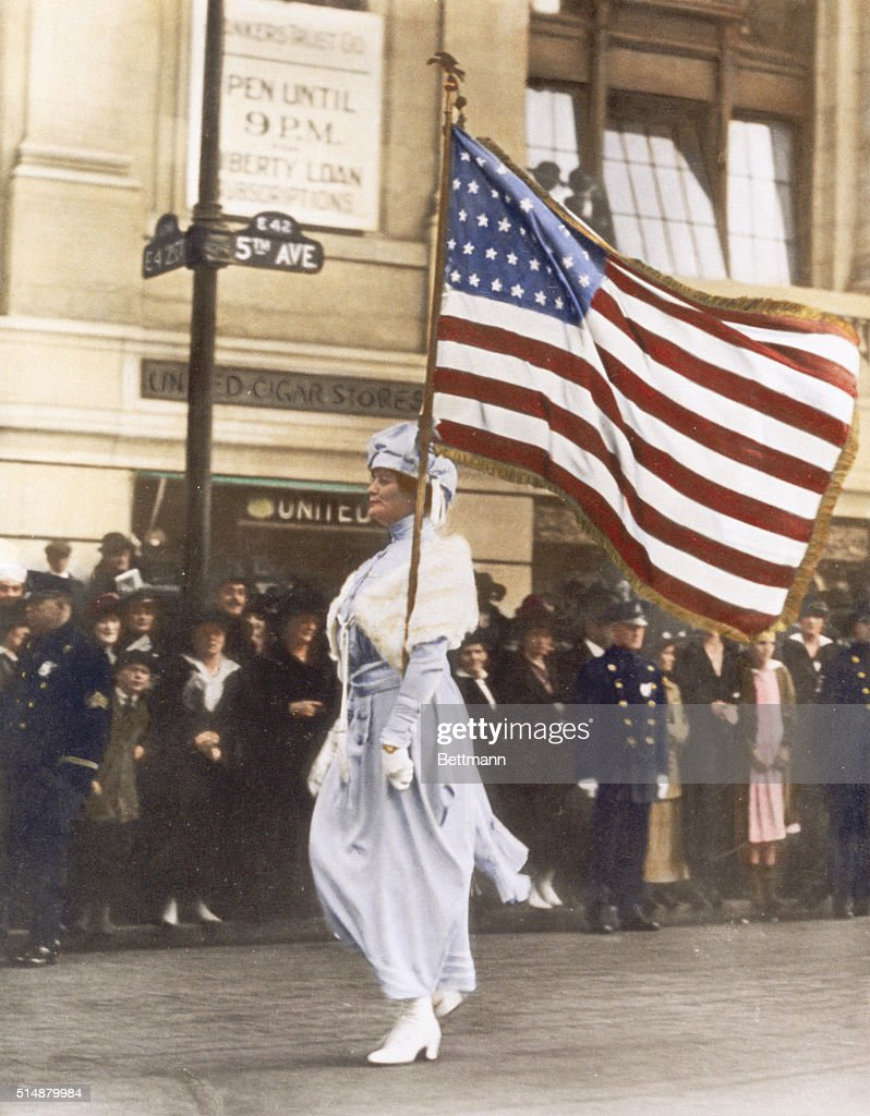 Mrs. Herbert Carpenter, bearing an American flag, marches in a parade for women's suffrage on Fifth Avenue in Manhattan.