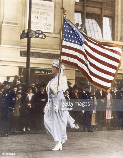 Mrs Herbert Carpenter bearing an American flag marches in a parade for women's suffrage on Fifth Avenue in Manhattan