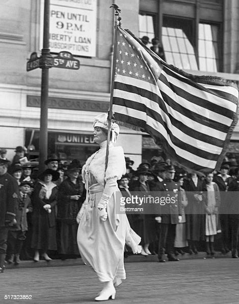 Mrs Herbert Carpenter bearing an American flag marches proudly at the head of a parade for women's suffrage on Fifth Avenue in Manhattan