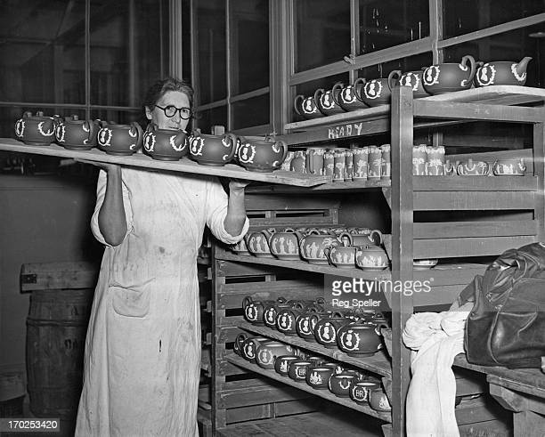 Mrs. Hilda Morgan prepares Coronation tea pots for the firing kiln at the Wedgwood works, Stoke-on-Trent, 1st December 1952. A variety of pottery and...