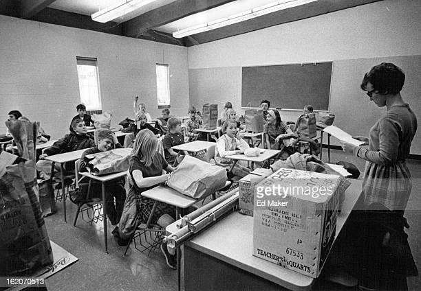 Mrs. Irene Tesitor, sixth grade teacher at Centennial School, reads instructions to the class in one of the classrooms they are using since moving.;
