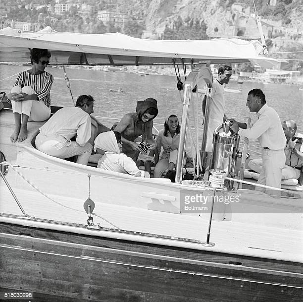 Mrs Jacqueline Kennedy checks over a camera before leaving on a daylong cruise aboard a yacht owned by the Gnelli family of Turin owners of the huge...