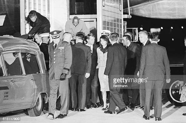 Mrs Jacqueline Kennedy her clothing splattered with the blood of her assassinated husband watches as the body of the dead President is placed in an...