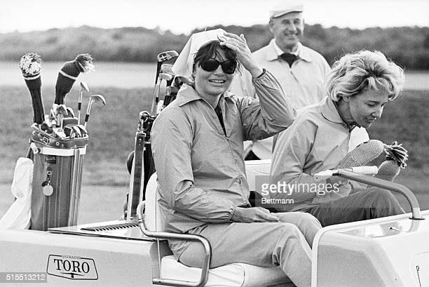 Mrs Jacqueline Kennedy pushes her hair back as she watched the President drive off the tenth tee during a round for the weekend at the home of Mrs...